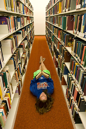 student lying down in library aisle